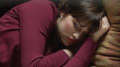 Close up panning shot of woman sleeping on sofa / Cedar Hills, Utah, United Stock Footage