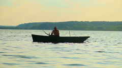Silhouette of lone fisherman sitting in boat, fishing equipment Stock Footage