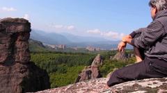 Man sitting on a rock and admiring the beautiful Belogradchik valley Stock Footage