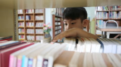 Little Asian child reading book in library Stock Footage