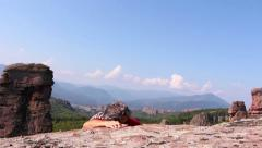 Man is climbing a rock and sitting to admire the beautiful Belogradchik valley Stock Footage