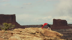 Wide shot of woman doing yoga on mountain / Moab, Utah, United States Stock Footage