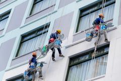 worker are painting the color in high rise buildings. - stock photo