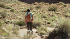Wide shot of woman hiker walking with dog / Moab, Utah, United States Stock Footage