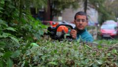 1. Gardener trimming hedge. Worker shaping bushy fence.Electric trimmer.Cutting. Stock Footage