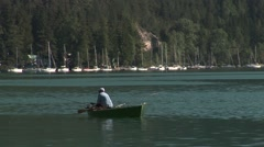 Fisher man fishing from his boat, in a lake in the alps. Stock Footage