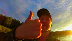 Male traveler showing thumbs up at camera, amateur video, fun Stock Footage