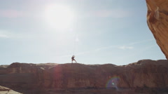 Wide tracking shot of man swinging from arch on rope / Corona Arch, Moab, Utah, - stock footage
