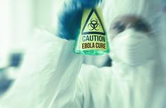Scientist in protective suit holding beaker Stock Photos
