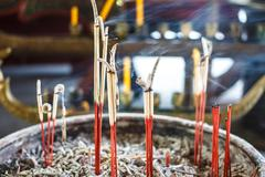 close up of burning incense sticks with smoke - stock photo