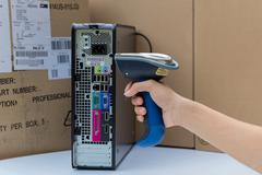 Holding and scanning label on the computer with bluetooth barcode scanner Stock Photos