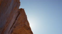 Wide tracking shot of man swinging from arch / Corona Arch, Moab, Utah, United - stock footage