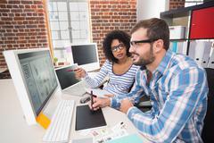 Photo editors using digitizer in office - stock photo