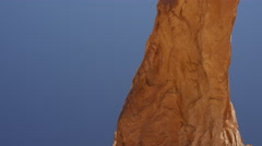 Slow motion wide tracking shot of man swinging from arch / Corona Arch, Moab, - stock footage