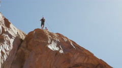 Wide tracking shot of man swinging from arch / Corona Arch, Moab, Utah, United Stock Footage