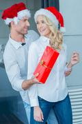 Playful man giving his wife a Christmas gift - stock photo