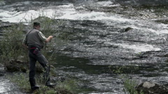Stock Video Footage of Fisherman in full equipment stand on rock
