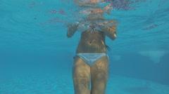 Beautiful slim girl in a white bikini swimming under water Stock Footage