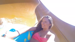 Girl rides on the slide/inflatable ring at the water park Stock Footage