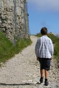 lonely child walks on the mountain path next to the huge wall of an ancient f - stock photo