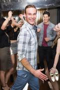 Stylish man smiling on the dancefloor - stock photo