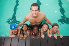 Stock Photo of Cute swimming class in pool with coach
