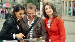 Happy tourist friends looking at map, guide in the city HD Stock Footage