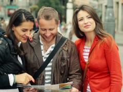 Happy tourist friends looking at map, guide in the city NTSC Stock Footage