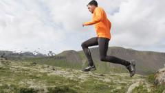 Stock Video Footage of Running man in cross country trail run jumping - Fit male runner in slow motion