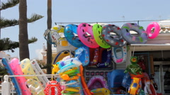 Colorful  beach toys blow in the breeze at the beach. Stock Footage