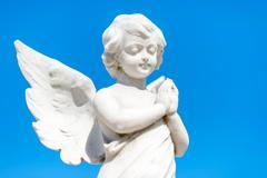 Beautiful infant angel on a blue sky Kuvituskuvat