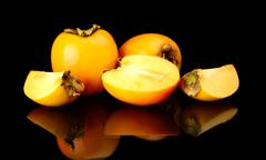 Few sharon kakis sliced-japanese persimmons,diospyros kakis isolated on black Stock Photos
