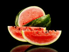 Studio shot of whole watermelon and slice of watermelon isolated on black bac Stock Photos