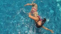 A woman playfully swimming in a pool Stock Footage