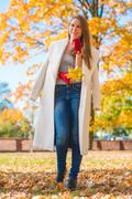 Pretty Woman in Big White Coat Holding Leaves Stock Photos