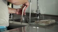 Man preparing, washing fish fillet in sink HD Stock Footage