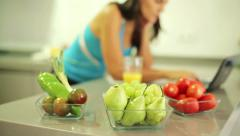 Bowls of fruits and vegetables, sporty woman in background HD - stock footage
