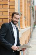 Confident bearded businessman with a newspaper Stock Photos