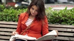 Young woman reading newspaper on bench in the city HD Stock Footage