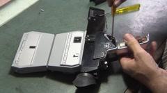 Camera Repair Technician with a bolex super 8 camera Stock Footage