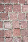 Old reddish stone pavement mounted on gravel Stock Photos