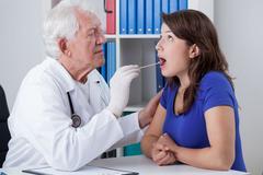 Stock Photo of general practitioner examining throat