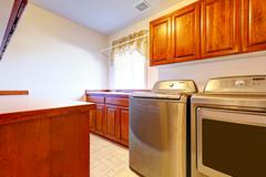 laundry room with modern steel appliances - stock photo