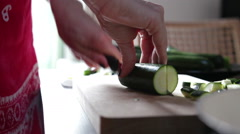 Woman cleaning and slicing zucchini for later cutting on cutting board - stock footage