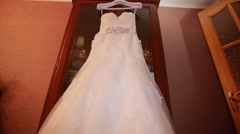 Wedding dress hanging on a cupboard Stock Footage