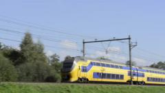 Dutch intercity double decker train on an elevated railroad track in the country Stock Footage