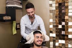 hairstylist hairdresser washing customer hair - stock photo
