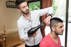 Hairdresser blow dry man's hair in shop Stock Photos