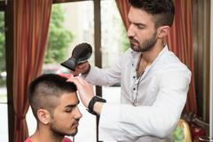 hairdresser blow dry man's hair in shop - stock photo