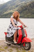Obese redhead beauty on a red scooter - stock photo